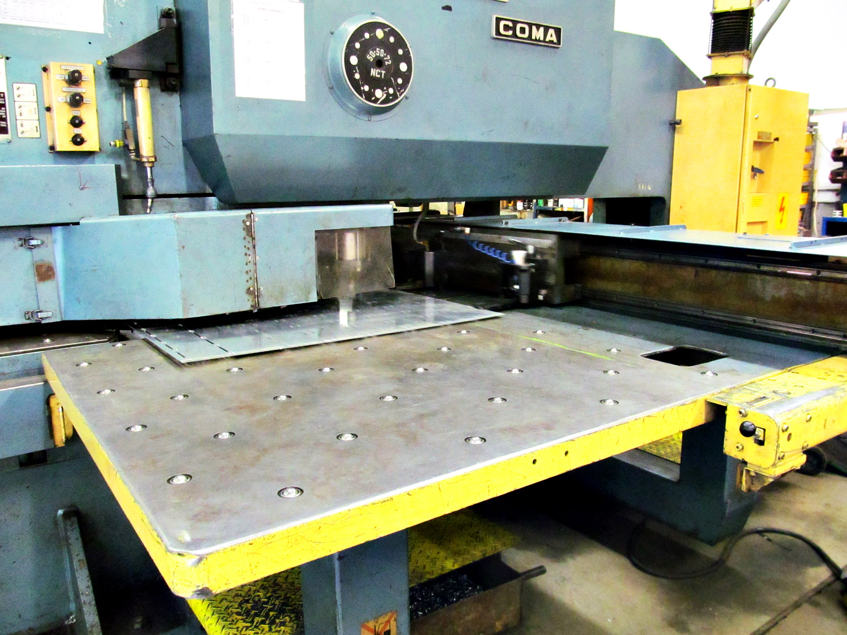 This is our turret punch press, punching through metal for custom parts creation at our sheet metal fab shop in Fremont Michigan.